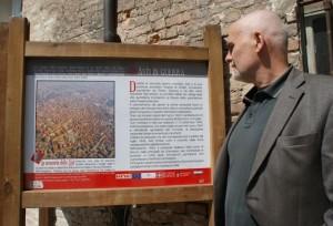 """Mario Renosio e uno dei pannelli della mostra """"Asti in guerra"""" allestita nel cortile di Palazzo Ottolenghi"""